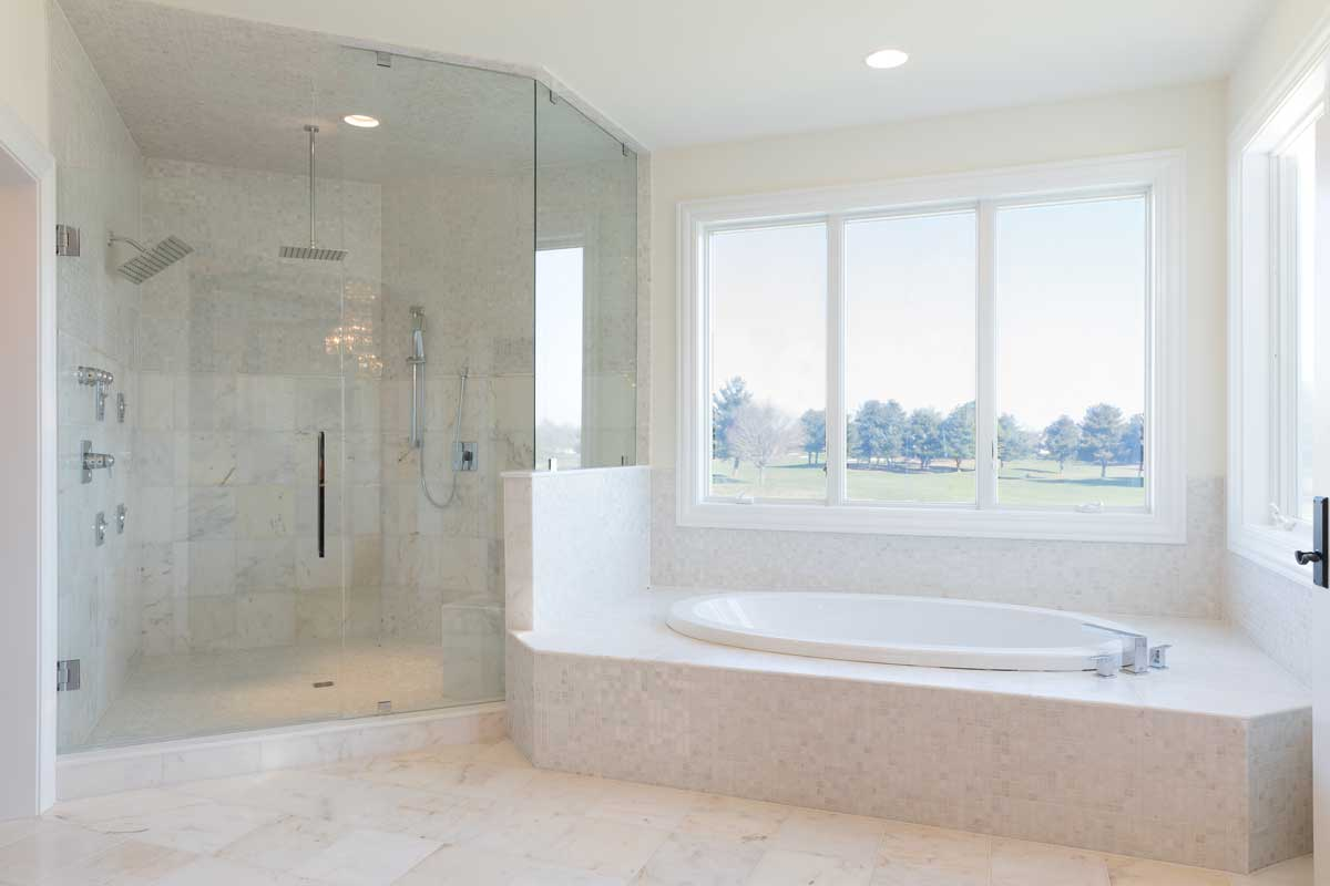 elegant master bathroom design with a white bath tub and glass shower and two vanity sinks
