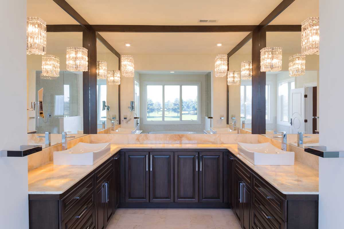 Elegant master bathroom with a double vanity with dark cabinets and two sinks and three mirrors