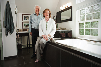 ellen cheever and pete giogi posing in a newly designed bathroom by Giorgi kitchens & designs