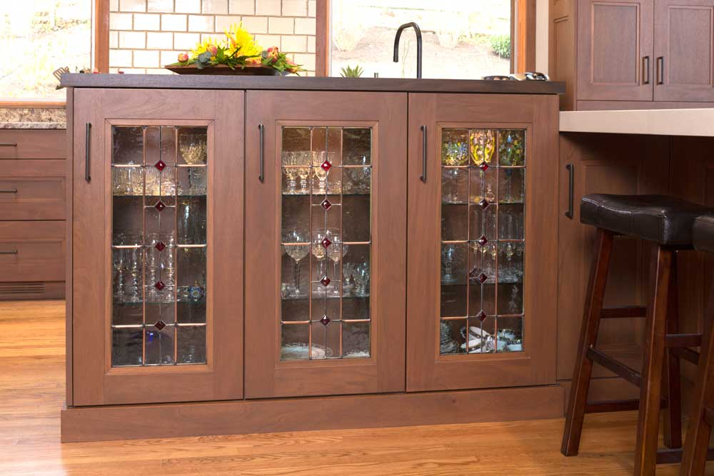 Modern Craftsman Kitchen with Mahogany Wood Cabinets with Three Glass Display Cabinets with Glassware Inside