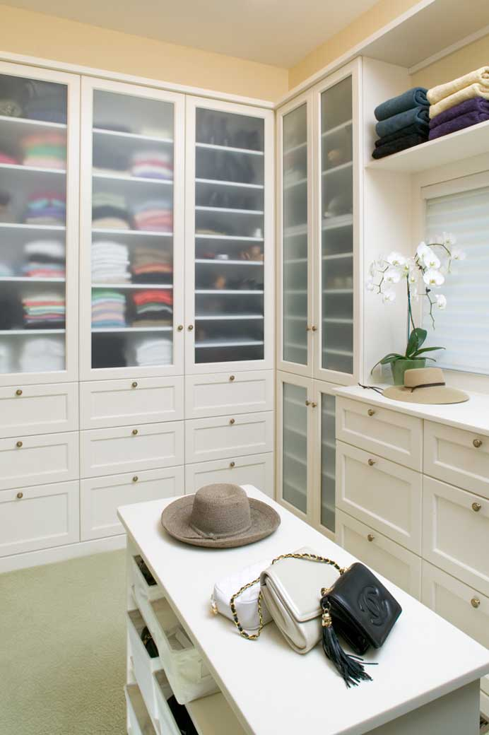 woman's closet of his hers closet has white cabinetry with frosted glass and a center island