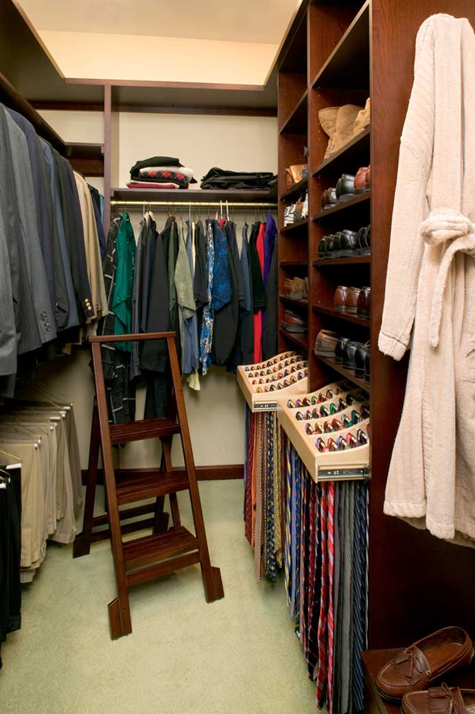 man's closet of his hers closet has dark wood open shelving and pull out tie racks
