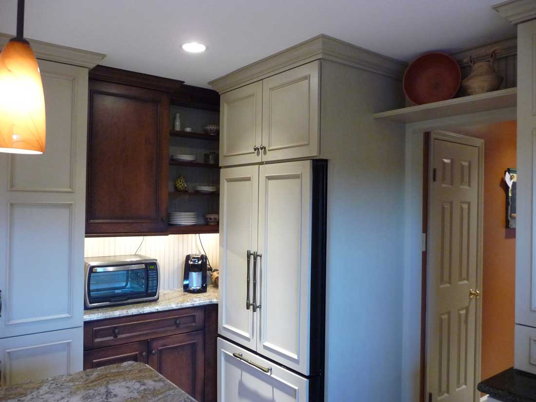 Kitchen Refrigerator behind a custom wood overlay in an off-white color with cabinet hardware
