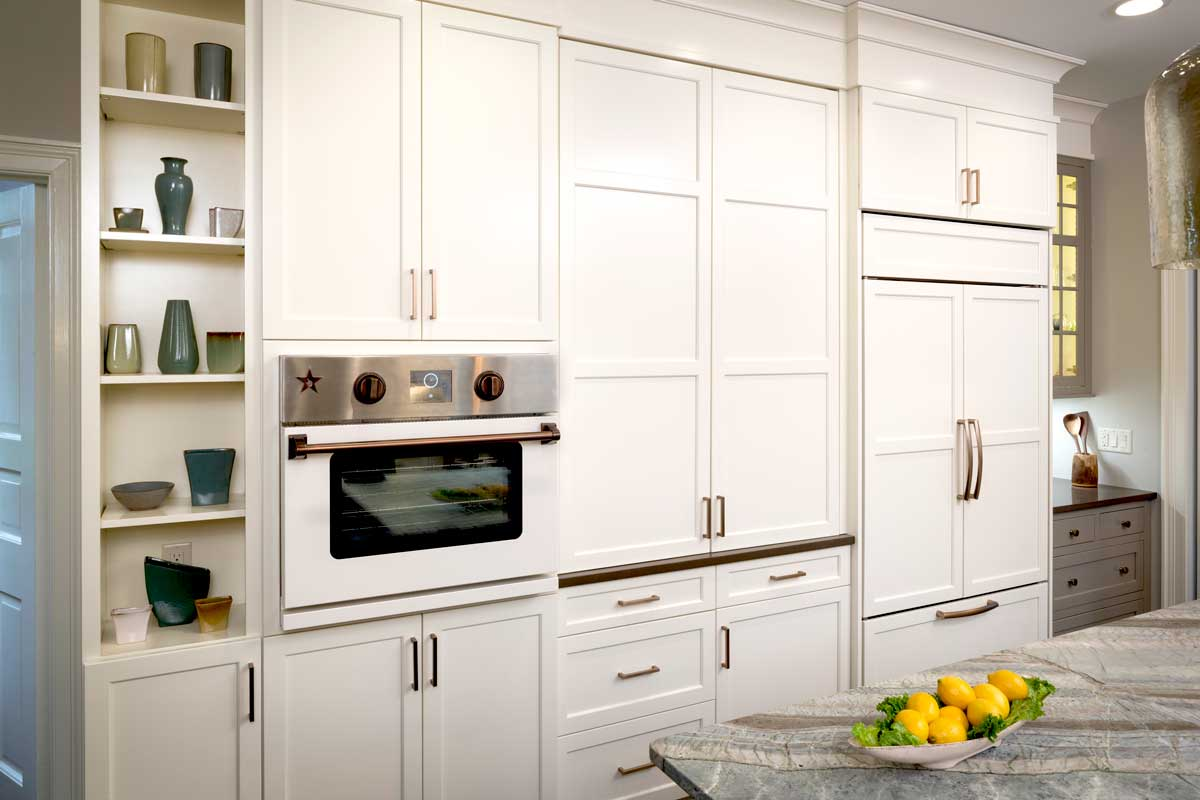 Tall white cabinets in a transitional kitchen design with kitchen copper accents and copper cabinet hardware
