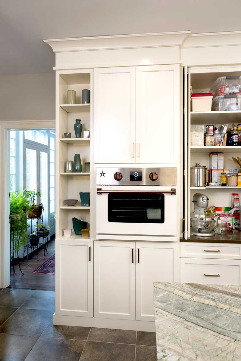 White cabinetry with hidden storage solutions including shelving and appliance storage and open shelving for pottery