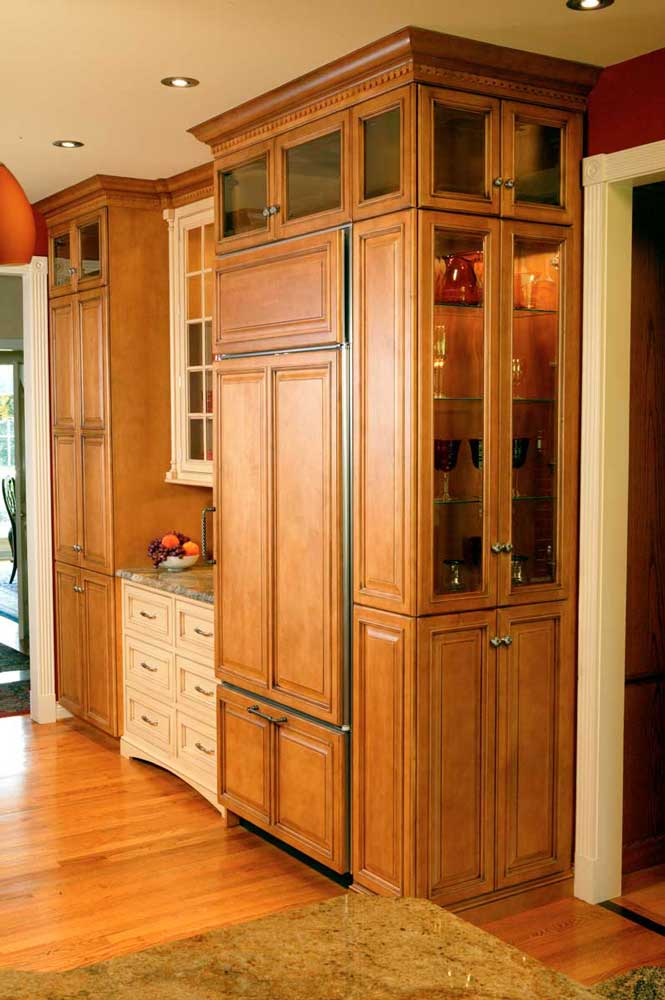 Wall length kitchen cabinetry houses glassware and a refrigerator in a Traditional Maple Kitchen