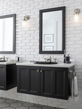Bathroom with white subway tile and dark vanities with mirrors and Kohler brand faucets in stainless-steel