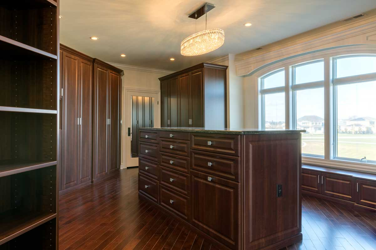large master closet design with dark wood cabinetry with cabinet storage solutions and a closet island