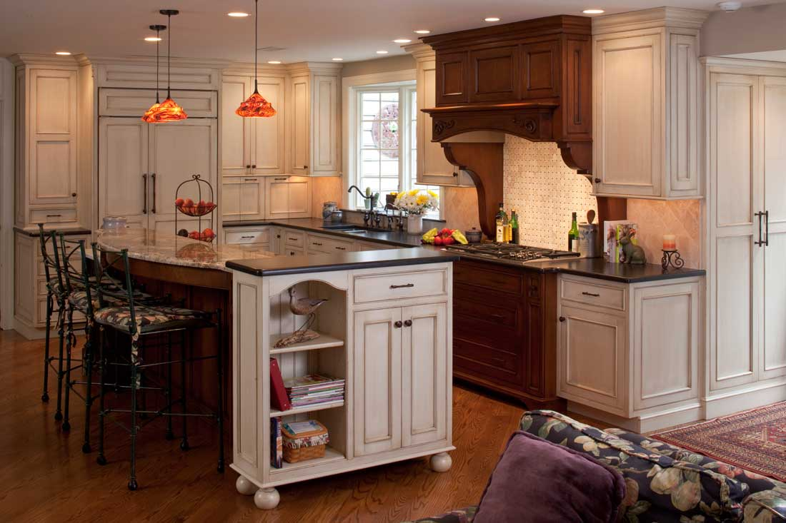Glazed white cabinets pair with custom medium brown cabinetry accent pieces in a traditional kitchen.