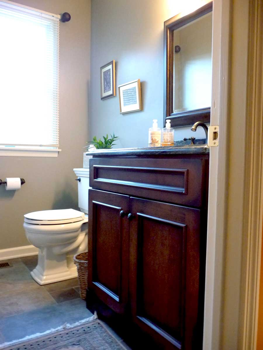 Cherry wood cabinets for a single vanity top in a traditional powder room design in Delaware