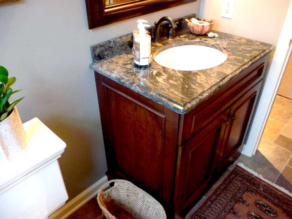 Dark Wood Cabinets Under Vanity with White Sink and Bronze Faucet for a Traditional Powder Room