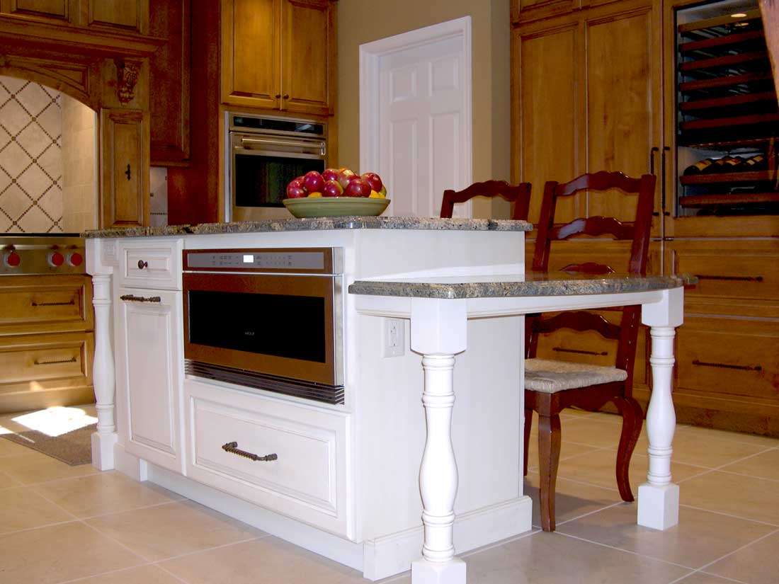 Traditional kitchen design with stainless steel kitchen appliances with white cabinetry for the multi-level kitchen island