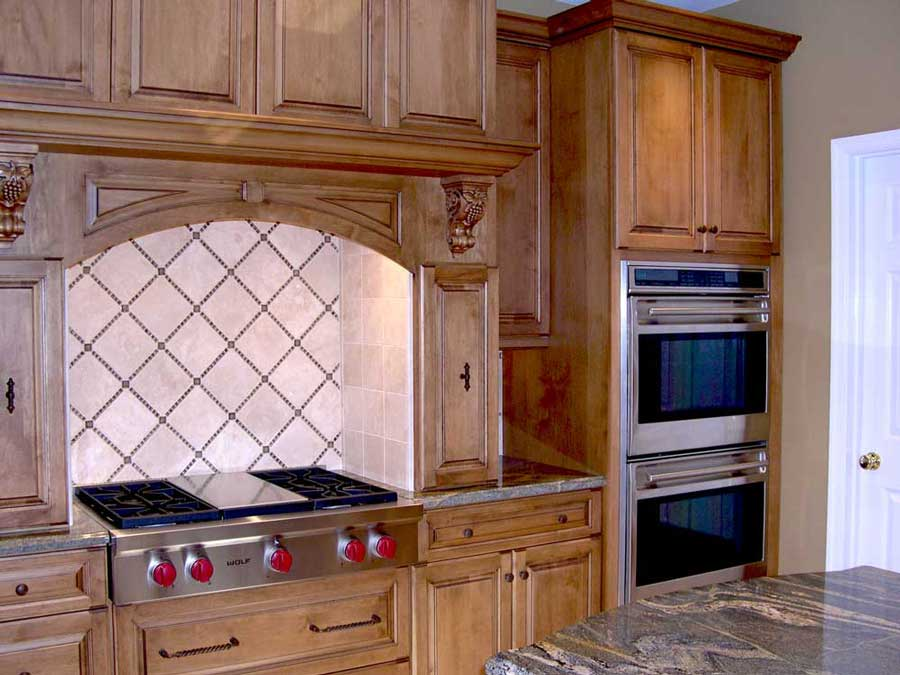Traditional kitchen design with stainless steel kitchen appliances with maple wood cabinets with custom range hood