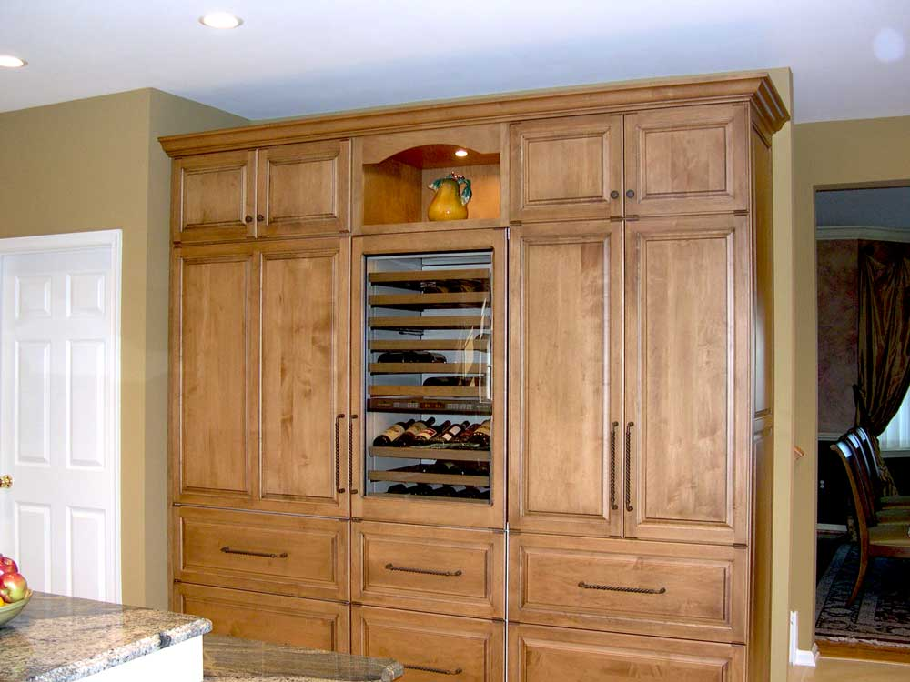 Maple wood ceiling high kitchen cabinetry with stainless steel kitchen appliances in a traditional kitchen design
