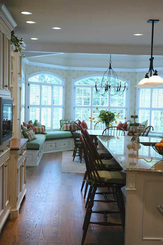 Traditional kitchen design with granite countertop island complete with class wood bar stools and pendant lighting.