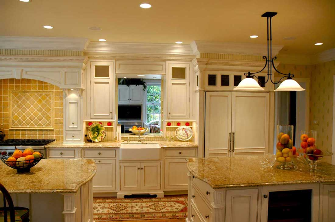 Traditional kitchen design featuring a white farmhouse sink, stone backsplash, and a variety of white cabinetry.