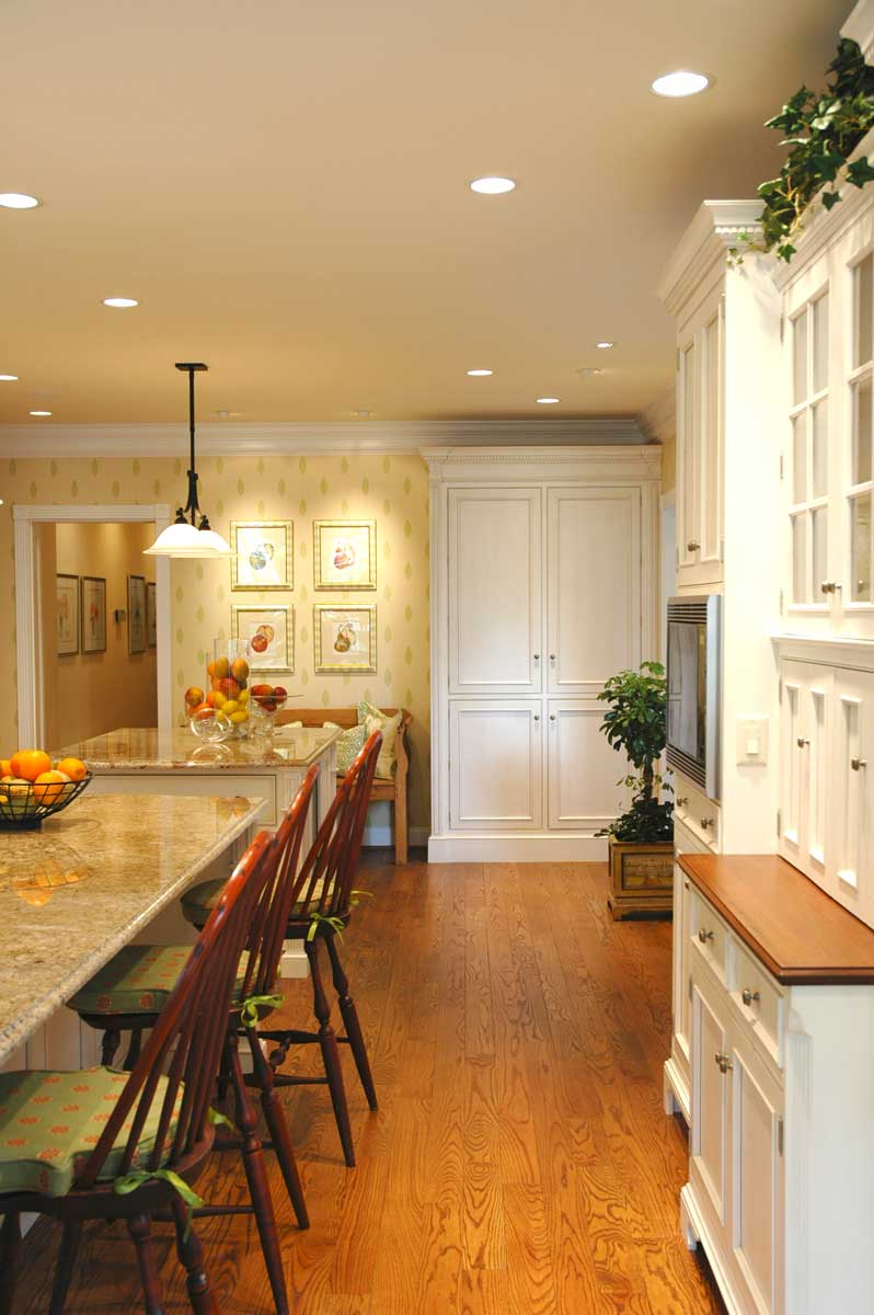 Wood cabinetry storage along the wall with wall oven in traditional kitchen design space.