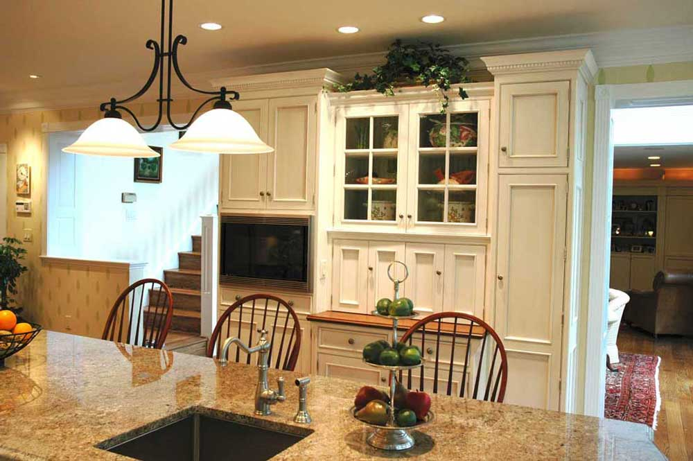 Custom white wall cabinetry with visible storage space for Colonial American traditional kitchen design.
