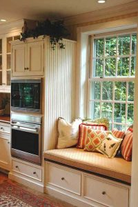 Comfortable window reading nook next to wall oven and cabinet area in traditional kitchen design.