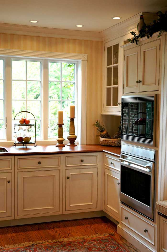 Large windows provide natural lighting near preparation and sink area of traditional kitchen design.