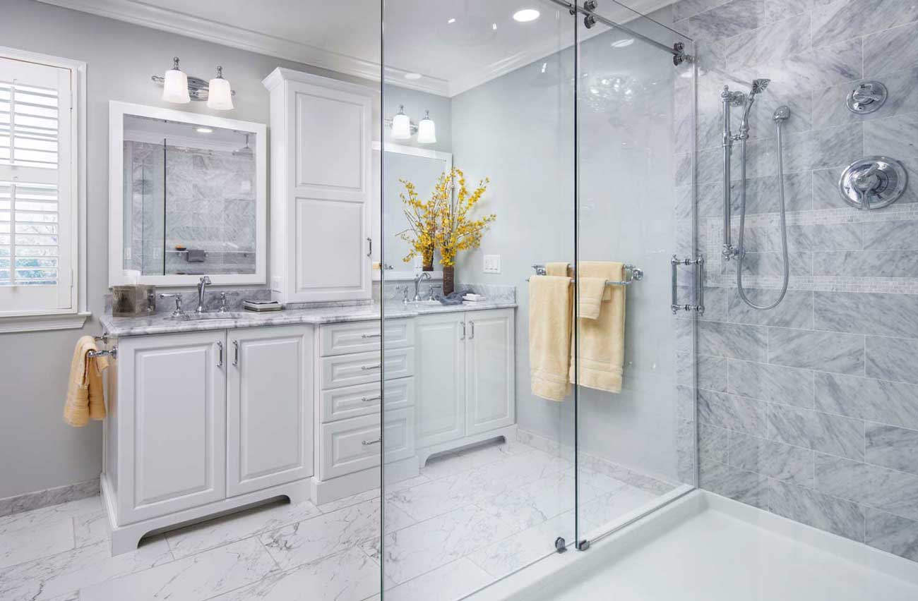 Large Glass Shower with a Double Vanity in a White Marble bathroom with yellow accent colors