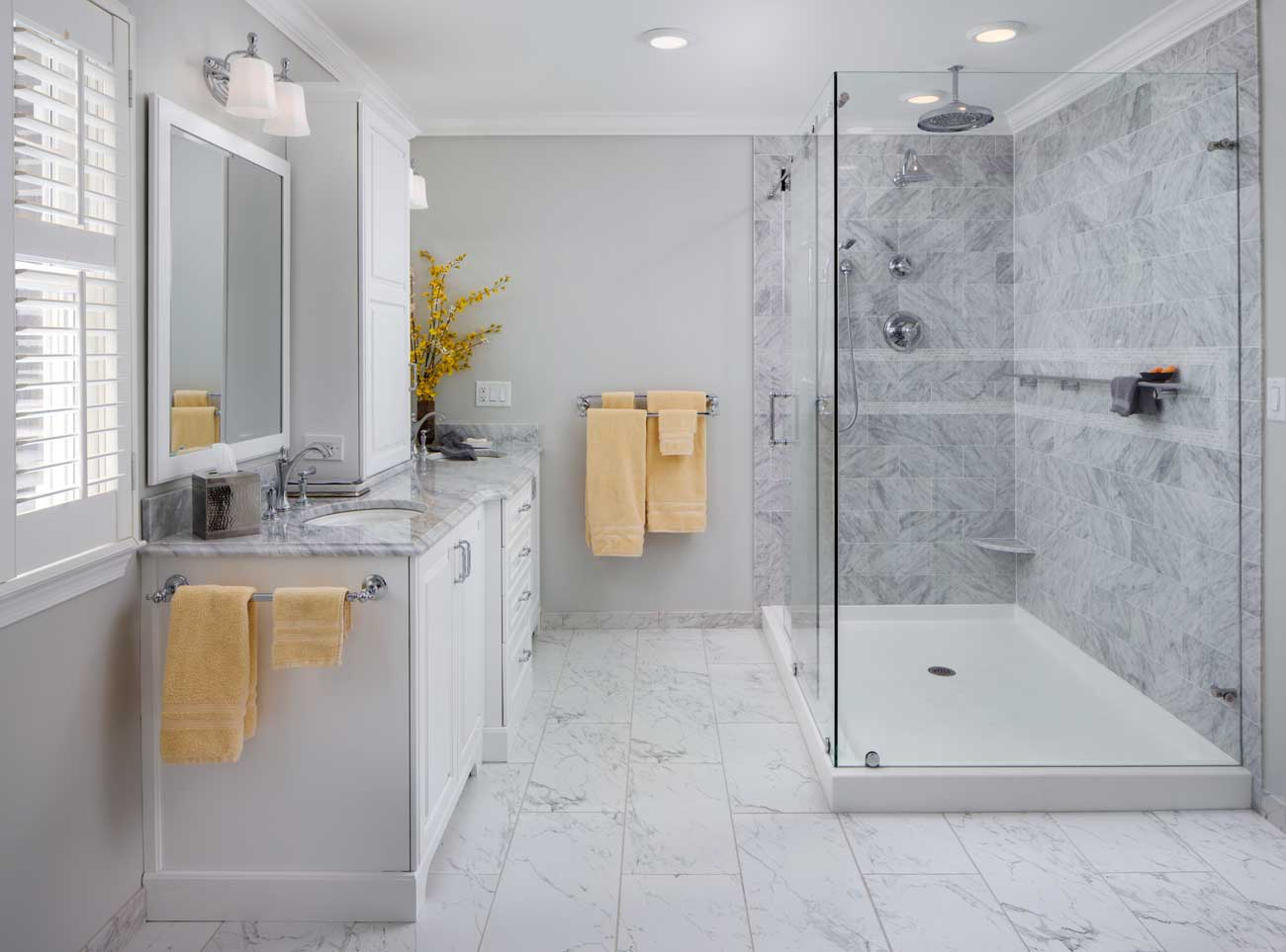 White Marble Bathroom with a Glass Shower and Yellow Accent Towels and Flowers in Wilmington, Delaware
