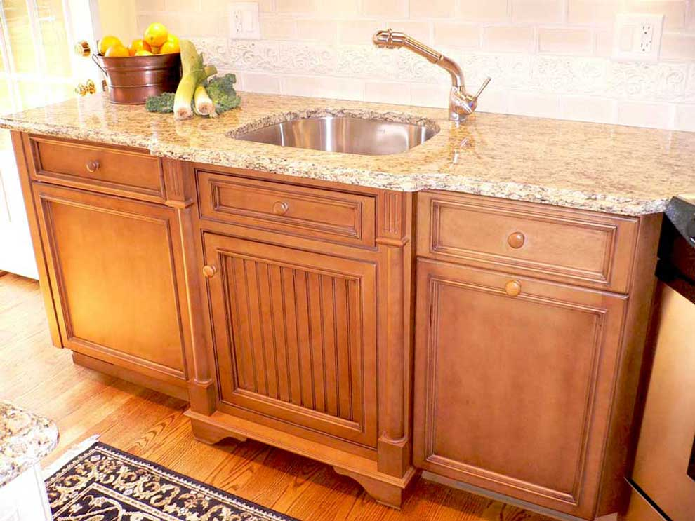 An undermount, stainless steel sink is placed inside Santa Cecelia Granite countertop on maple kitchen cabinets