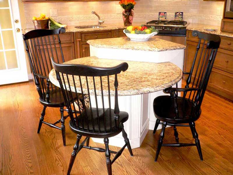 Traditional black chairs administer practical seating for the lower island eating area for three people