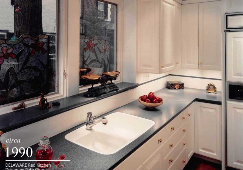 White vintage kitchen accented with red decor and hardwood flooring, complete with a two bowl sink